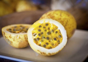 Cut and whole passion fruit served on a plate. Passion fruit, a fragrant tropical fruit common in tropical locations. Photographed close-up in Kauai, Hawaii in horizontal format.
